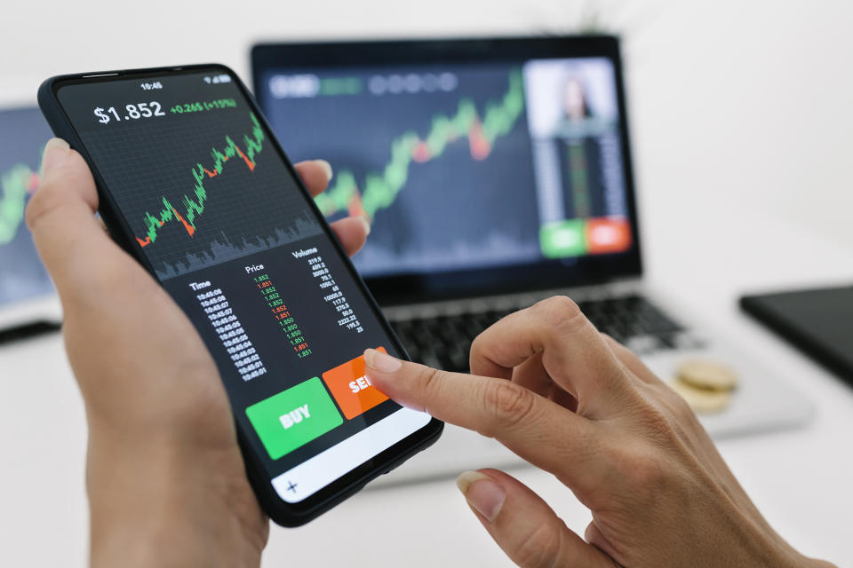 Female manager selling cryptocurrencies through mobile phone app. Stock market, investment and cryptocurrencies concept