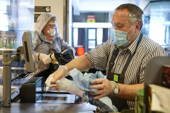A Waitrose employee cleans a check out: Getty Images