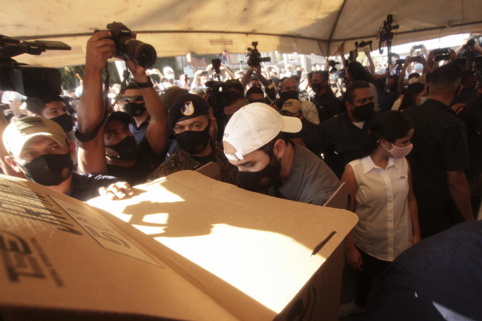 President Nayib Bukele prepares his ballots behind a privacy screen as he votes in local and legislative elections, in San Salvador, El Salvador, Sunday, Feb. 28, 2021. El Salvador went to the polls in legislative and mayoral elections that could break the congressional deadlock that has tied the hands of President Bukele.(AP Photo/Salvador Melendez)