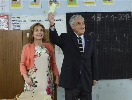 Chile's President Pinera accompanied by first lady Morel shows his vote during the presidential election at a school in Santiago