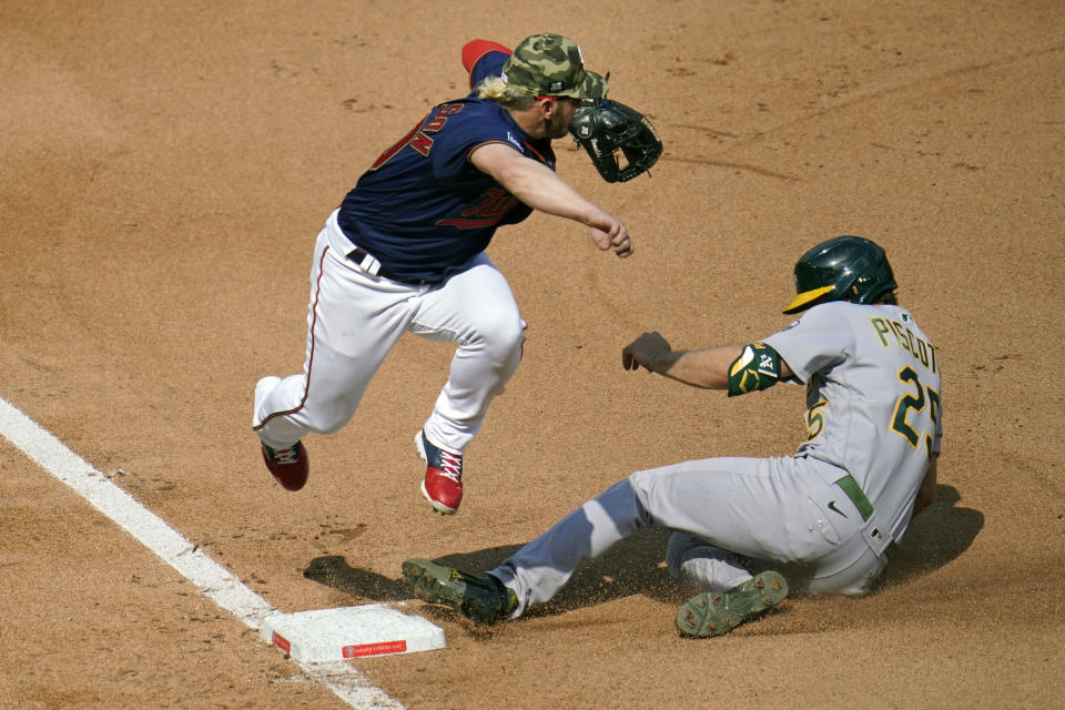 Minnesota Twins third baseman Josh Donaldson, leaps clear of Oakland Athletics' Stephen Piscotty, right, as Piscotty advances to third from second after tagging up on a fly ball by Chad Pinder in the fourth inning of a baseball game, Saturday, May 15, 2021, in Minneapolis. (AP Photo/Jim Mone)