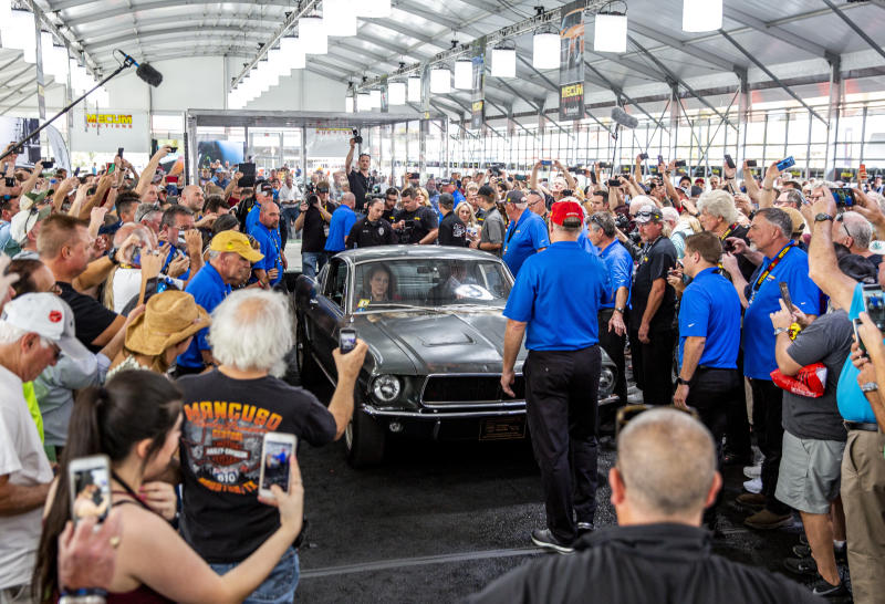 "People surround the 1968 ""Bullitt"" Mustang GT car, Friday, Jan 10, 2020 in Kissimmee, Fla. The iconic Highland Green 1968 Mustang GT that once made history for its appearance in the film ""Bullitt"" is now making history again. It fetched $3.74 million Friday at Mecum's Kissimmee auction, making it the most expensive Mustang ever sold. (Patrick Connolly/Orlando Sentinel via AP)"