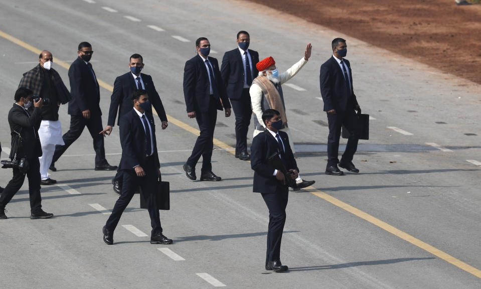 Indian Prime Minister Narendra Modi, red cap, waves as he returns after India's Republic Day celebrations in New Delhi, India, Tuesday, Jan.26, 2021. Republic Day marks the anniversary of the adoption of the country's constitution on Jan. 26, 1950. (AP Photo/Manish Swarup)