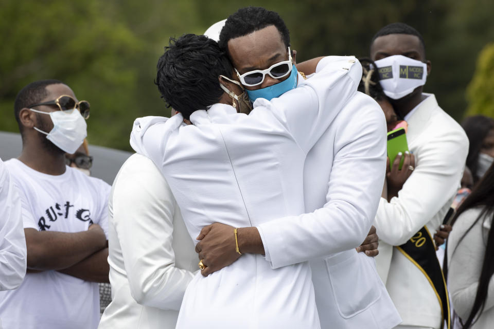 """Surrounded by masked mourners in precaution of the coronavirus, Iran """"Bang"""" Paylor, of Washington, is comforted during the interment service of his mother, Joanne Paylor, 62, of Washington, at Lincoln Memorial Cemetery, in Suitland-Silver Hill, Md., Sunday, May 3, 2020. The family delayed Paylor's funeral for almost two months hoping the social distancing rules would be lifted. Despite not having died from coronavirus, almost every aspect of his mother's funeral has been impacted by the pandemic. (AP Photo/Jacquelyn Martin)"""