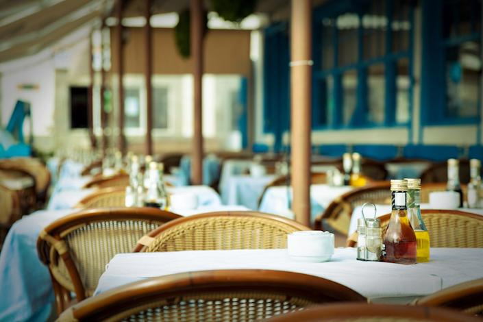 """Some jurisdictions are instituting protocols that make it harder for patrons to be in close quarters. <p class=""""copyright""""><a href=""""http://www.shutterstock.com/pic-151519028/stock-photo-empty-tables-at-an-outdoor-restaurant.html?src=7QC0kaLKG1lRFoTXkE7Haw-1-5"""" rel=""""nofollow noopener"""" target=""""_blank"""" data-ylk=""""slk:Shutterstock"""" class=""""link rapid-noclick-resp"""">Shutterstock</a></p>"""