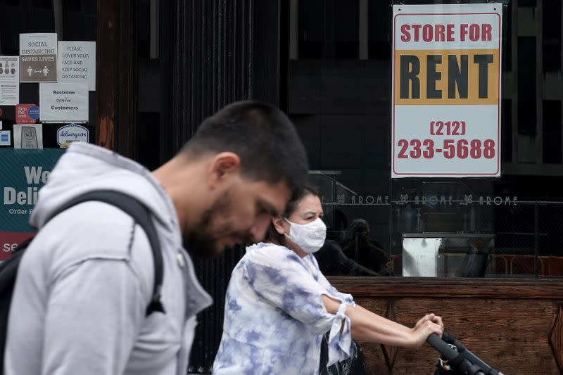 FILE PHOTO: People walk past a shuttered store in New York City