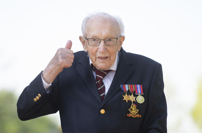 99-year-old war veteran Captain Tom Moore, poses for a photo at his home in Marston Moretaine, England, after he achieved his goal of 100 laps of his garden, raising millions of pounds for the NHS with donations to his fundraising challenge from around the world, Thursday April 16, 2020. Moore started walking laps in his garden as a humble fundraising challenge to walk 100 lengths of his garden by his 100th birthday on April 30, and has now raised millions for the National Health Service and become a national rallying point during the COVID-19 coronavirus pandemic.  His family thought it would be a stretch to raise 1,000 pounds, but donors have pledged millions of pounds and still counting. (Joe Giddens/PA via AP)