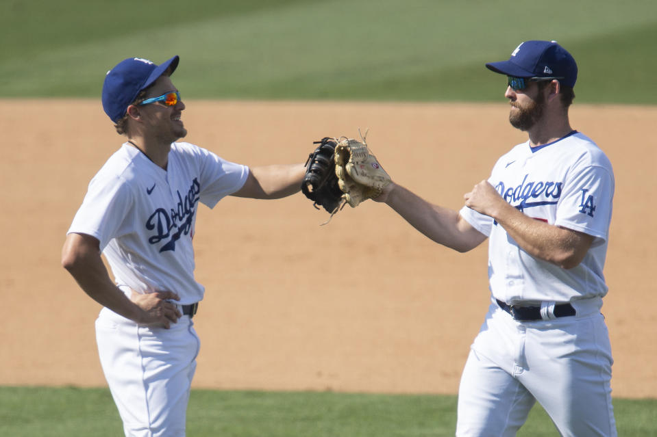 Los Angeles Dodgers first baseman Enrique Hernandez, left, and right fielder Adam Kolarek celebrate their win over the Los Angeles Angels in a baseball game in Los Angeles, Sunday, Sept. 27, 2020. (AP Photo/Kyusung Gong)
