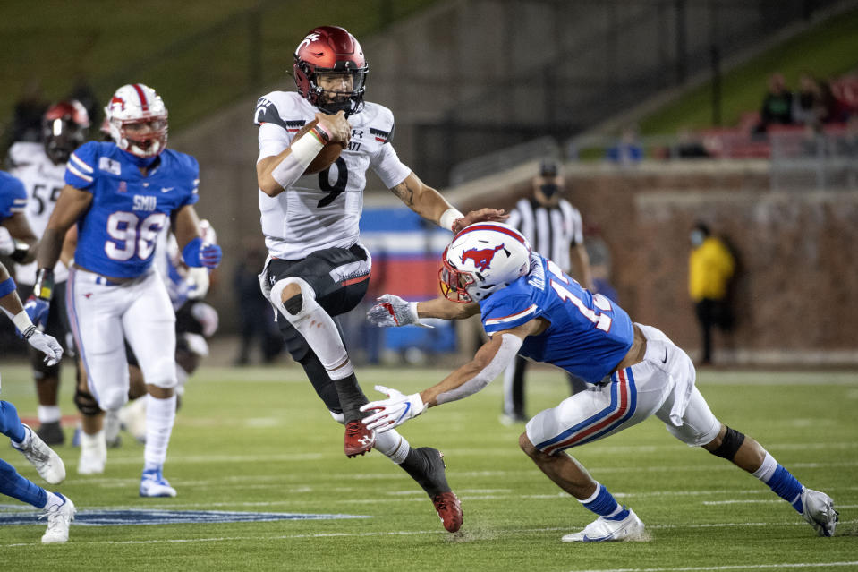 Cincinnati quarterback Desmond Ridder (9) evades the tackle of SMU safety Roderick Roberson, Jr. (13) on a touchdown run during the second half of an NCAA college football game Saturday, Oct. 24, 2020, in Dallas. (AP Photo/Jeffrey McWhorter)