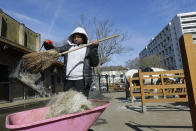 Zion Mcleod, 13, sweeps up at Ebony Horse Club in Brixton, south London, Sunday, April 18, 2021. In the midst of south London's hustle and bustle, only a 10-minute walk from a subway station, is a school where children are encouraged to horse around. The Ebony Horse Club provides 140 rides per week to children in the local community offering them the opportunity to learn important life skills along with horseback riding. (AP Photo/Kirsty Wigglesworth)