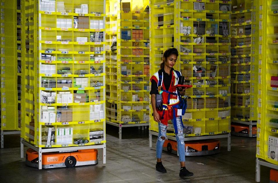 Amazon employee Deasahni Bernard moves among robots at the 855,000-square-foot Amazon fulfillment center in Staten Island February 5, 2019 (AFP Photo/Johannes EISELE)