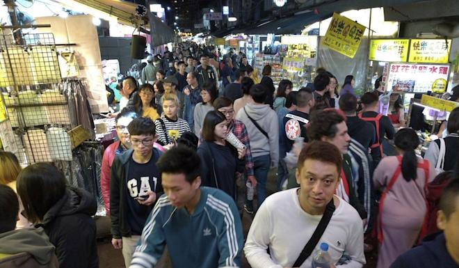 Locals and tourists visit a night market in Taipei. Photo: AP