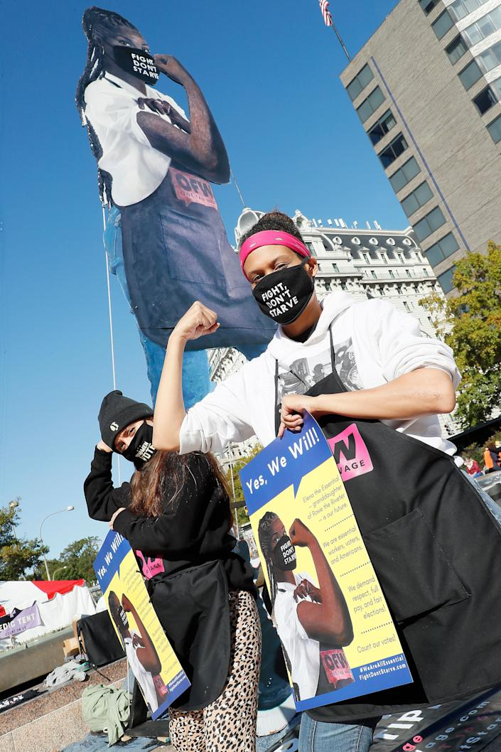 One Fair Wage team members Breanne Delgado (left) and Nikki Cole (right) rally at the base of an 18-foot wooden statue of Elena the Essential, representing service worker's demand for respect, full pay and fair elections as part of the protests on Saturday. (Photo: Paul Morigi via Getty Images)