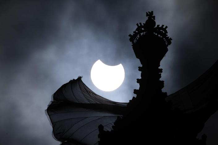 A partial solar eclipse is seen over the Houses of Parliament in London.