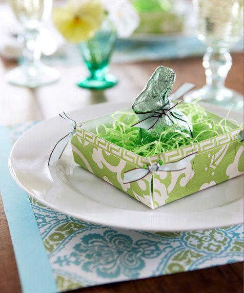 """<p>A patterned paper plate creates a fresh-as-spring table setting. For the basket, flip a 7-inch square plate over; cut out a 1 1/2-inch square from each corner. Fold up the sides of the plate as shown; with hole punch, create two adjacent holes at corners. Thread in 3 inches of ribbon and knot. Fill with paper grass and a chocolate rabbit. Then craft a disposable placemat from inexpensive wrapping paper: To do: Trace a standard 12"""" x 16"""" mat onto the back of your paper (opt for heavier stock papers for best results); cut out placemat. To create a trim, snip out a strip of solid colored paper roughly an inch wide and as tall as your placemat (12 inches). Affix with double-sided tape under the strip.</p>"""