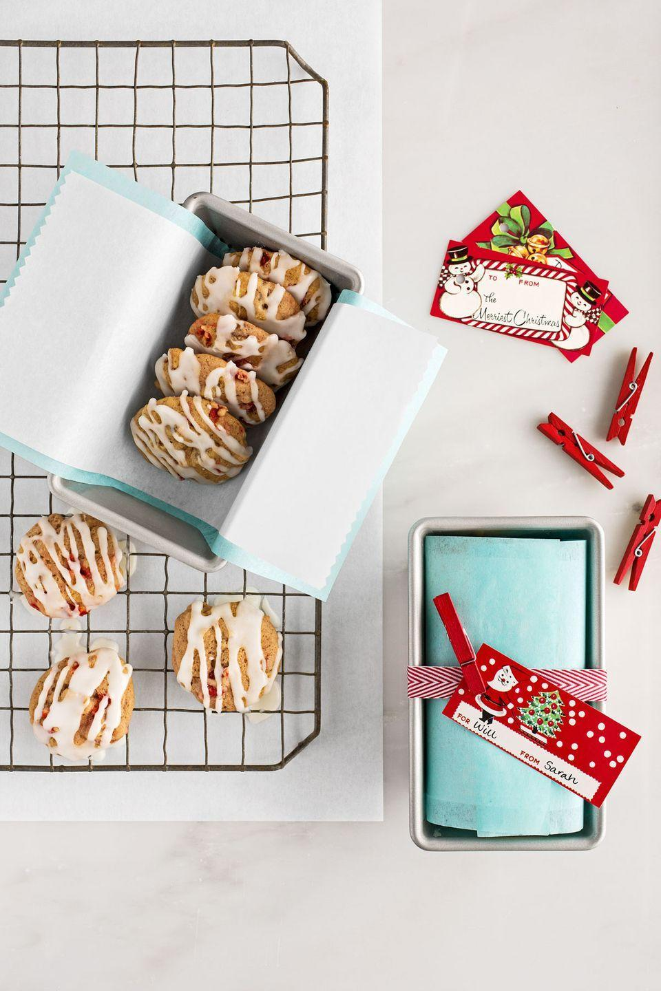 """<p>Line a mini loaf pan, with plain tissue paper then wax paper. Add cookies, fold over paper, then wrap with ribbon and attach a card with a mini clothespin.</p><p><strong><a href=""""https://www.countryliving.com/food-drinks/recipes/a36899/fruitcake-cookies/"""" rel=""""nofollow noopener"""" target=""""_blank"""" data-ylk=""""slk:Get the recipe"""" class=""""link rapid-noclick-resp"""">Get the recipe</a>.</strong></p><p><a class=""""link rapid-noclick-resp"""" href=""""https://www.amazon.com/Chicago-Metallic-Commercial-Non-Stick-Mini/dp/B003YKGQVK/?tag=syn-yahoo-20&ascsubtag=%5Bartid%7C10050.g.647%5Bsrc%7Cyahoo-us"""" rel=""""nofollow noopener"""" target=""""_blank"""" data-ylk=""""slk:SHOP MINI LOAF PANS"""">SHOP MINI LOAF PANS</a></p>"""