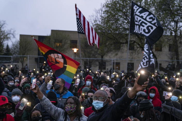 Demonstrators flash their mobile phone lights as they gather outside the Brooklyn Center Police Department to protest Sunday's fatal shooting of Daunte Wright during a traffic stop, Tuesday, April 13, 2021, in Brooklyn Center, Minn. (AP Photo/John Minchillo)