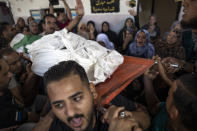 Mourners carry the body of Palestinian Hamas militant, Mohammad Abu Namous, 27, out of the family home during his funeral in the Jabaliya refugee camp, northern Gaza Strip, Sunday, Aug. 18, 2019. Gaza's Health Ministry said Israeli troops killed three Palestinians and severely wounded a fourth near the heavily guarded perimeter fence. The Israeli military said Sunday that a helicopter and a tank fired at a group of armed suspects near the fence overnight. (AP Photo/Khalil Hamra)