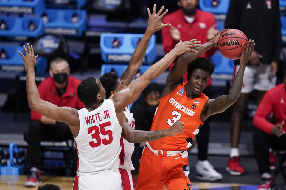 Syracuse forward Kadary Richmond (3) looks to pass against Houston forward Fabian White Jr. (35) and Marcus Sasser (0) in the first half of a Sweet 16 game in the NCAA men's college basketball tournament at Hinkle Fieldhouse in Indianapolis, Saturday, March 27, 2021. (AP Photo/Michael Conroy)