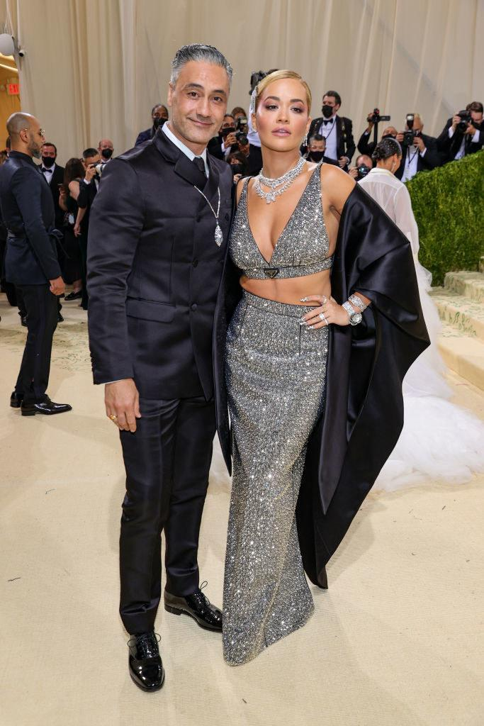 Taika Waititi wears a dark suit and Rita Ora wears a floor length sparkly skirt and matching cropped tank top