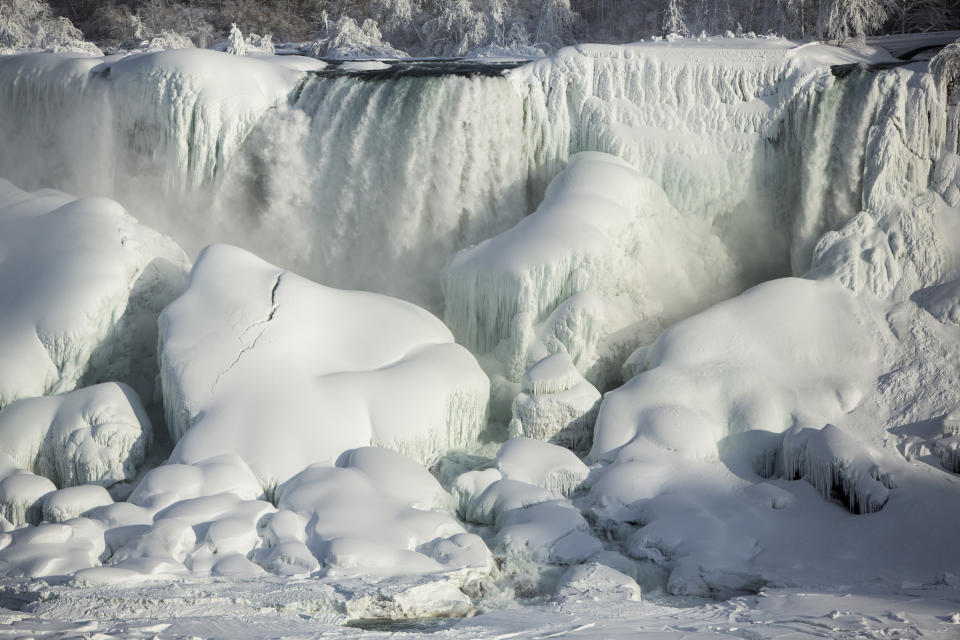A partially frozen American Falls in sub freezing temperatures is seen in Niagara Falls, Ontario February 17, 2015. Temperature dropped to 6 degrees Fahrenheit (-14 Celsius) on Tuesday. The National Weather Service has issued Wind Chill Warning in Western New York from midnight Wednesday to Friday.   REUTERS/Lindsay DeDario  (CANADA - Tags: TRAVEL ENVIRONMENT)