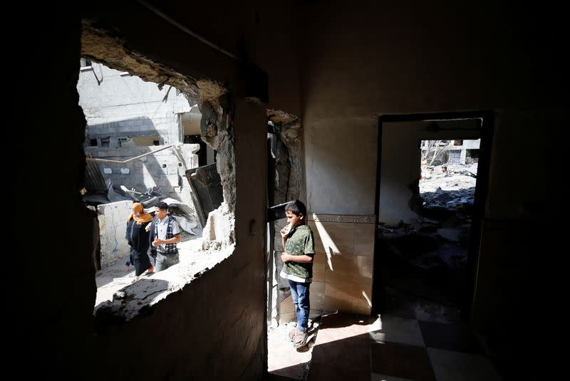 A Palestinian boy stands inside a house which was damaged by Israeli air strikes