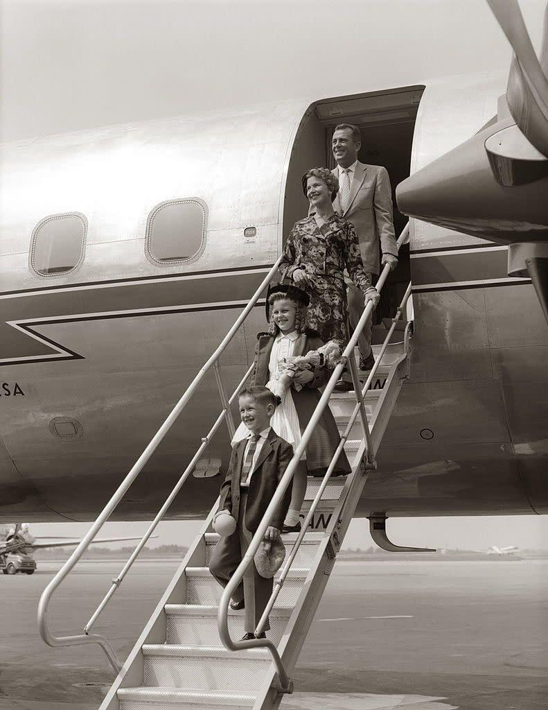A family walking down airplane stairs.