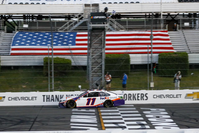 "<a class=""link rapid-noclick-resp"" href=""/nascar/sprint/drivers/1283/"" data-ylk=""slk:Denny Hamlin"">Denny Hamlin</a> gets the checkered flag as he crosses the finish line to win the NASCAR Cup Series auto race at Pocono Raceway, Sunday, June 28, 2020, in Long Pond, Pa. (AP Photo/Matt Slocum)"