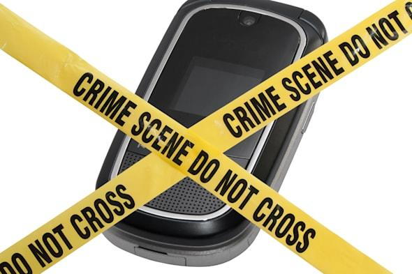 A mobile cell phone is blocked by yellow police tape reading Crime Scene Do Not Cross. The concept represents compromised techno
