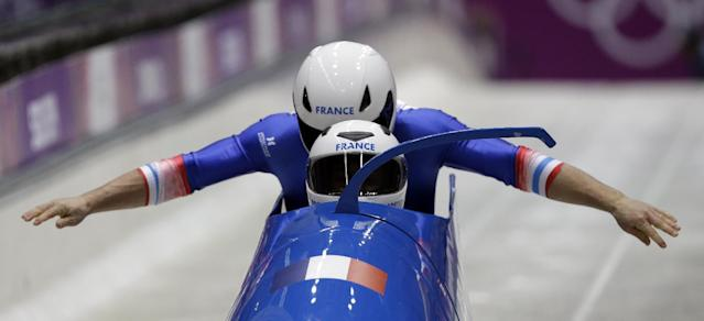 The team from France FRA-1, piloted by Loic Costerg and brakeman Romain Heinrich, start their first run during the men's two-man bobsled competition at the 2014 Winter Olympics, Sunday, Feb. 16, 2014, in Krasnaya Polyana, Russia. (AP Photo/Dita Alangkara)