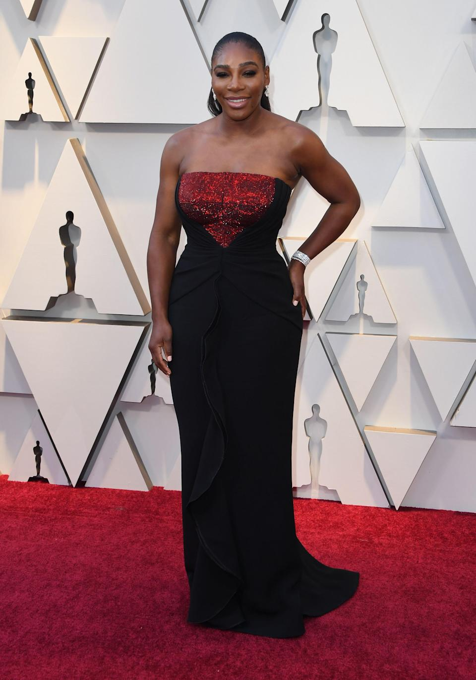 <p>The tennis pro, who presented an award, wowed in a strapless black gown boasting red, sequin detailing on the bodice. <em>[Photo: Getty]</em> </p>