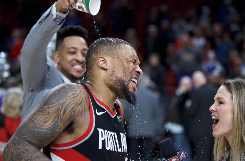 Portland Trail Blazers guard Damian Lillard, center, gets doused by guard CJ McCollum after Lillard scored 61 points against the Golden State Warriors in an NBA basketball game in Portland, Ore., Monday, Jan. 20, 2020. The Trail Blazers won 129-124 in overtime. (AP Photo/Craig Mitchelldyer)