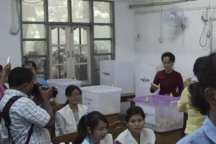 Onlookers peer through a window as Myanmar opposition leader and head of the National League for Democracy (NLD), Aung San Suu Kyi (R), casts her vote at a polling station in Yangon, on November 8, 2015 (AFP Photo/Nicolas Asfouri)