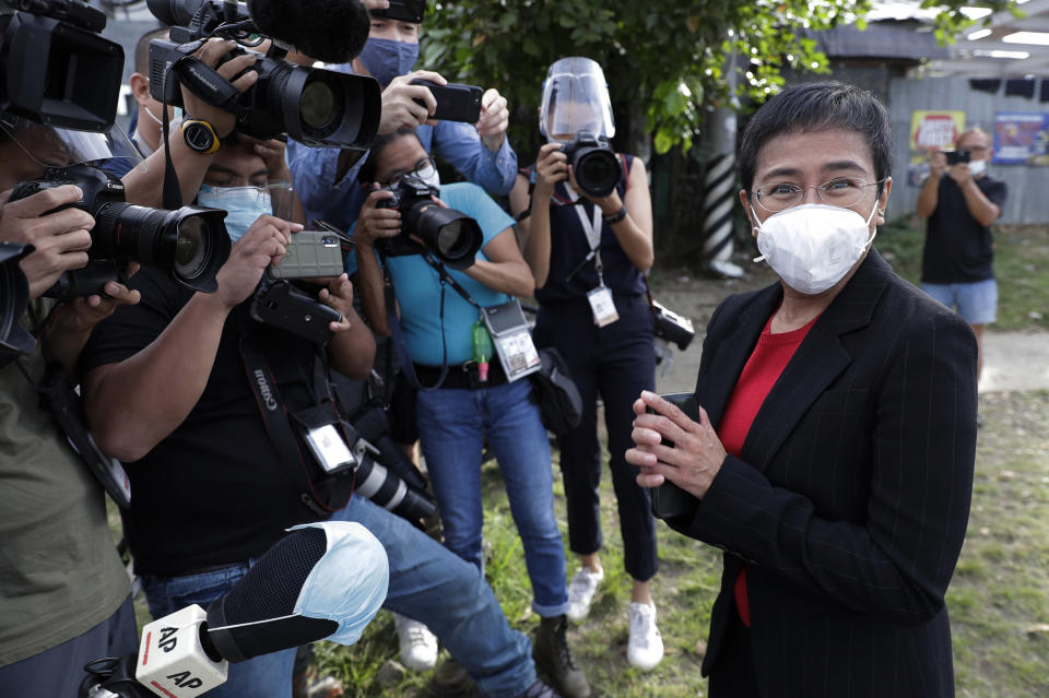FILE - In this March 4, 2021, file photo, Rappler CEO and Executive Editor Maria Ressa, right, wearing a face mask to prevent the spread of the coronavirus, stands in front of reporters as she arrives at the Court of Tax Appeals in Metro Manila, Philippines. The Nobel Peace Prize was awarded to journalists Ressa of the Philippines and Dmitry Muratov of Russia for their fight for freedom of expression. (AP Photo/Aaron Favila, File)