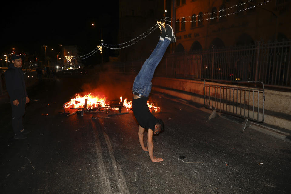 A Palestinian protester does a handstand next to a fire which was set on a road during clashes with Israeli police near Damascus Gate just outside Jerusalem's Old City, Sunday, May 9, 2021. Israeli police have been clashing with Palestinian protesters almost nightly in the holy city's worst religious unrest in several years. (AP Photo/Ariel Schalit)