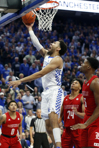 Kentucky's EJ Montgomery, middle, shoots between Louisville's Lamarr Kimble (0), Dwayne Sutton (24) and Steven Enoch (23) during the first half of an NCAA college basketball game in Lexington, Ky., Saturday, Dec. 28, 2019. (AP Photo/James Crisp)