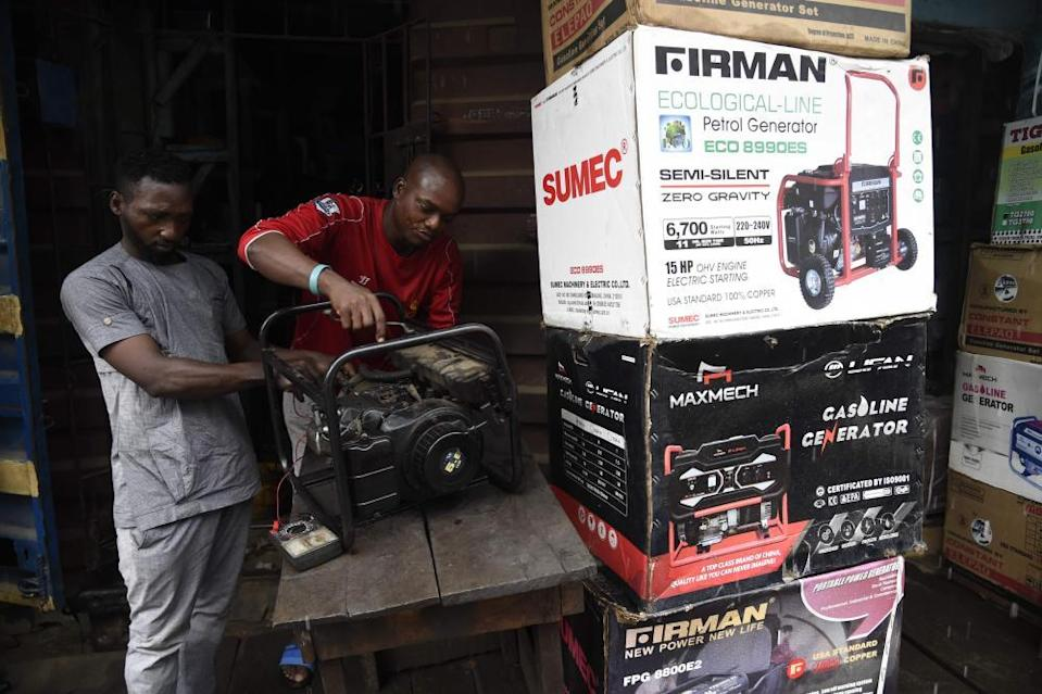 NIGERIA-ECONOMY-OIL-ELECTRICITYTechnicians repair a generator in a shop at Yaba district of Lagos, on September 9, 2020. - The Nigerian government has dumped a decade-long pricing regime for petrol and electricity allowing marketers to fix prices resulting in anger and tension in the oil-rich Africa's most populous country of 200 million people. (Photo by PIUS UTOMI EKPEI / AFP) (Photo by PIUS UTOMI EKPEI/AFP via Getty Images)
