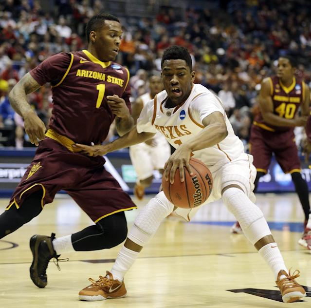 Texas guard Isaiah Taylor (1) drives against Arizona State guard Jahii Carson (1) during the first half of a second-round game in the NCAA college basketball tournament Thursday, March 20, 2014, in Milwaukee. (AP Photo/Jeffrey Phelps)
