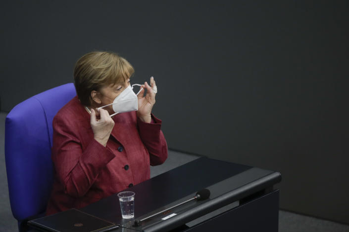German Chancellor Angela Merkel adjusts her face mask as she arrives for a parliament session about a new law to battle the coronavirus pandemic at the Bundestag at the Reichstags building in Berlin, Germany, Friday, April 16, 2021. (AP Photo/Markus Schreiber)