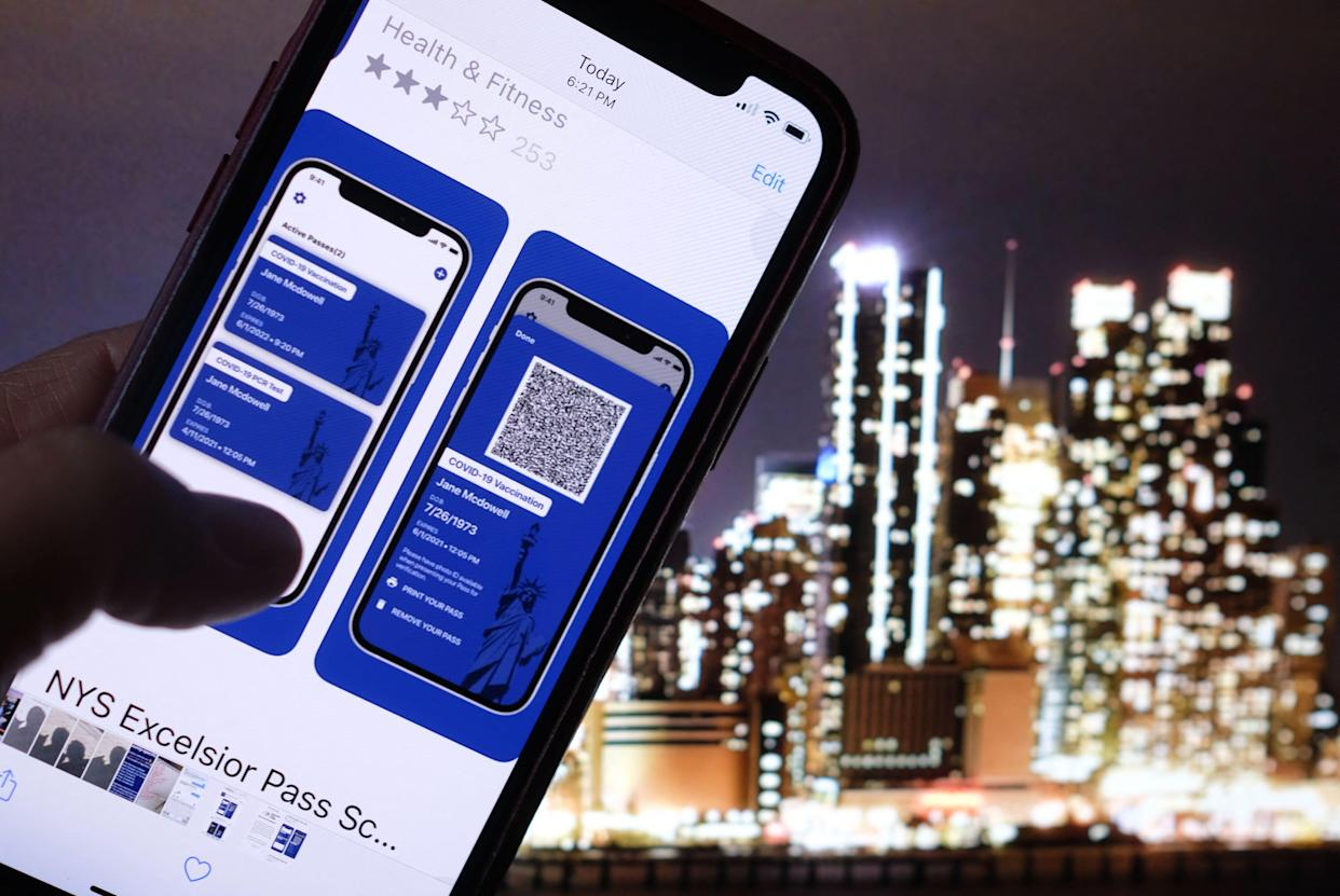 TOPSHOT - This illustration photo taken in Los Angeles on April 6, 2021 shows a person looking at the app for the New York State Excelsior Pass, which provides secure, digital proof of a Covid-19 vaccination, in front of a screen showing the New York skyline. - As the United States' vaccination campaign accelerates, so-called vaccine passports are gaining traction despite political divisions and a fragmented health care system that complicates the centralization of data. (Photo by Chris DELMAS / AFP) (Photo by CHRIS DELMAS/AFP via Getty Images)