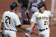Pittsburgh Pirates' Bryan Reynolds, right, is greeted by Jacob Stallings after scoring on a sacrifice fly by Colin Moran during the third inning against the Cincinnati Reds in a baseball game in Pittsburgh, Wednesday, Sept. 15, 2021. All Pirates players wore No. 21 in honor of Roberto Clemente Day. (AP Photo/Gene J. Puskar)