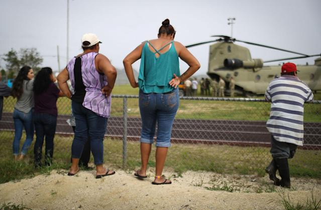 <p>Local residents watch after a U.S. Army helicopter landed during food and water delivery efforts four weeks after Hurricane Maria struck on Oct. 18, 2017 in Utuado, Puerto Rico. U.S. soldiers and agents delivered supplies provided by FEMA to remote residents in mountainous Utuado. (Photo: Mario Tama/Getty Images) </p>