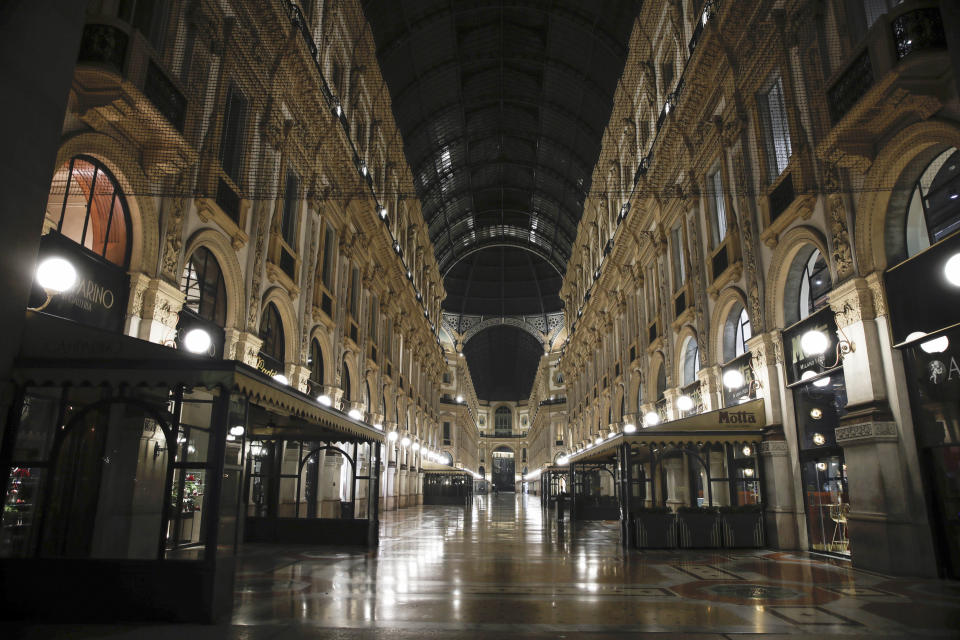 The Vittorio Emanuele II arcarde is deserted, in Milan, northern Italy, early Sunday, Oct. 25, 2020. Since the 11 p.m.-5 a.m. curfew took effect last Thursday, people can only move around during those hours for reasons of work, health or necessity. (AP Photo/Luca Bruno)