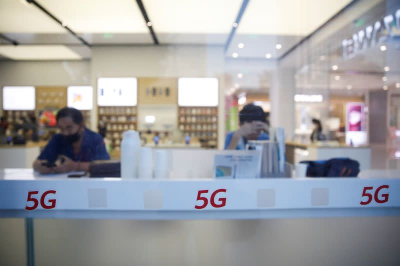People wearing face masks are seen next to 5G signs on a Huawei store at a shopping mall, in Beijing