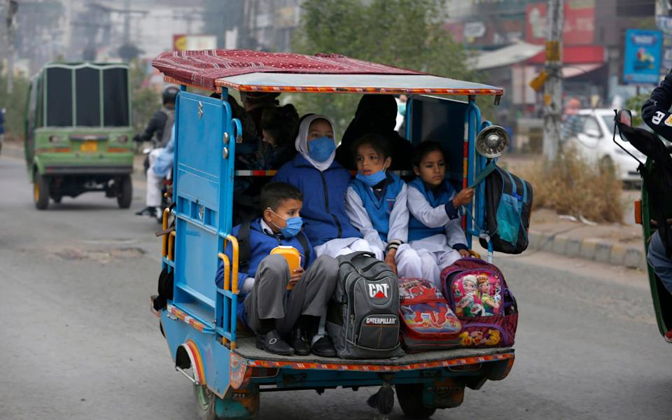 Students wearing face masks to protect against the coronavirus, ride in a tri-wheeler to school in Lahore, Pakistan - K. M. Chaudary/AP