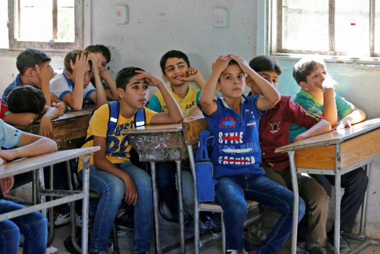 Syrian students from the former rebel held area of Eastern Ghouta attend class at a school in Kafr Batna on September 5, 2018