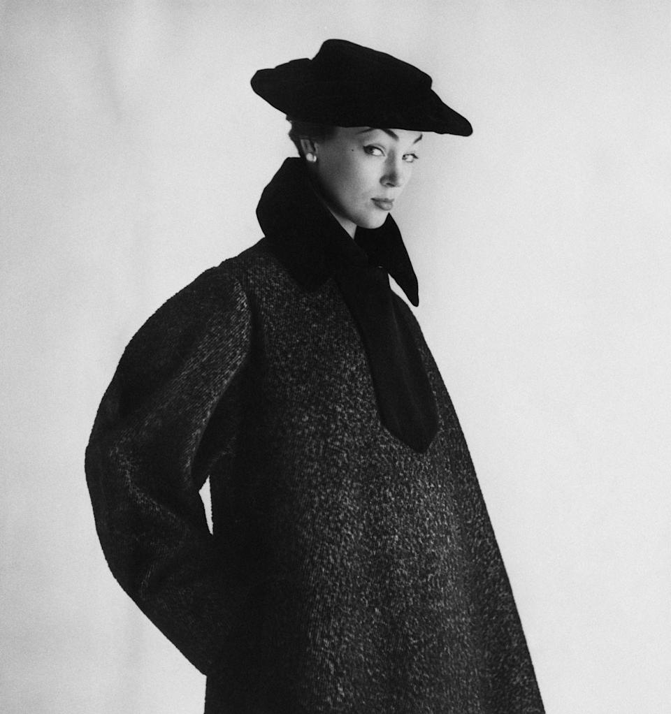<p>A women modeling a velvet-trimmed gray coat with a cap-effect silhouette. </p>
