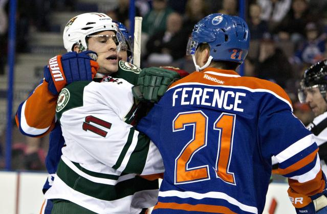 Minnesota Wild's Zach Parise (11) and Edmonton Oilers' Andrew Ference (21) mix it up during first period NHL hockey action in Edmonton, Alberta, on Tuesday Jan. 27, 2015. (AP Photo/The Canadian Press, Jason Franson)