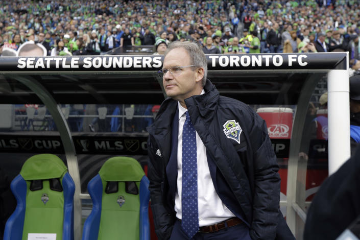 FILE - In this Sunday , Nov. 10, 2019 file photo, Seattle Sounders Brian Schmetzer stands next to the bench before the MLS Cup championship soccer match against Toronto FC in Seattle. The Seattle Sounders are known for making the Major League Soccer postseason in each year of the club's existence. The team has also shown the ability to correctly assess when it needs to overhaul its personnel, whether it's bringing in an influx of fresh talent or giving younger players in the system a chance. That's the decision the Sounders made going into the 2021 season. (AP Photo/Ted S. Warren, File)