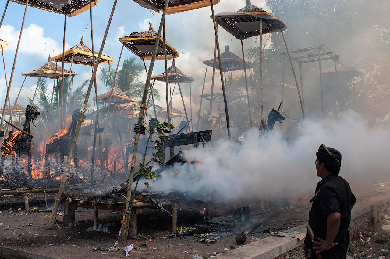 UBUD, BALI, INDONESIA - AUGUST 18: A man watches the sarcophagi burn at the cremation site during a Balinese Hindu mass cremation on August 18, 2013 in Ubud, Bali, Indonesia. More than 60 corpses were collectively cremated to share the expense of the ceremony. Well known as Ngaben, it is one of the most important ceremonies for Balinese Hindu people, as they believe it will free the spirit from the deceased body so it can reincarnate. (Photo by Putu Sayoga/Getty Images)